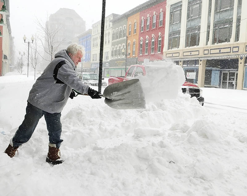Brad Shaw shovels a path to the door of his Fussbudget's Sports Card shop around 12:25 p.m. on Saturday.