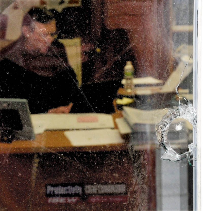 Staff photo by David Leaming CLOSE CALL AGAIN: A hole from a BB gun is seen in one of five windows damaged at the International Brotherhood of Electrical Workers Local 1253 office in Fairfield as Training Director Christopher Trider works inside on Monday, Feb. 11, 2013.