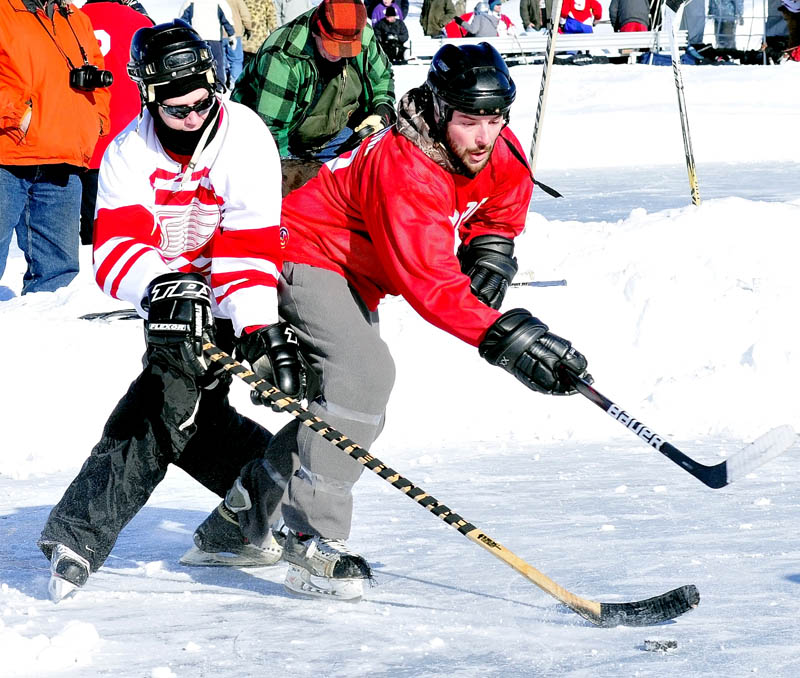 CLASSIC: Jeff Browne, right, of the Winslow-based Cioppa team, battles for possession of the puck with a Portland area player during the Maine Pond Hockey Classic on Sunday on China Lake. Cioppa finished runner-up to Hart Construction.