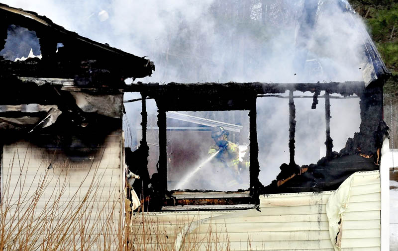 A firefighter can be seen through burned-out windows and walls while fighting a fire that destroyed a mobile home in Sidney on Tuesday.