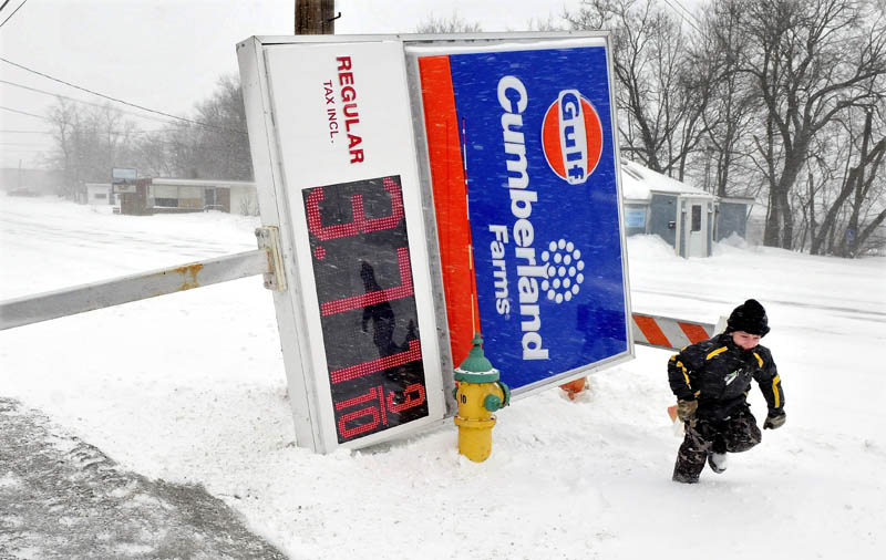 Liam Poulin runs back to his father's plowtruck after looking at the fallen sign at Cumberland Farms in Waterville. A store worker said the sign fell to the ground during strong winds before dawn on Saturday.