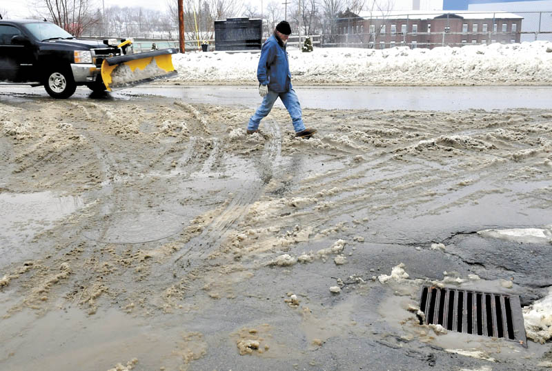 Don Holmes searches for dry ground while crossing a slush-covered street in Anson on Thursday. Warm temperatures turned a predicted snowstorm into a rainstorm yesterday.