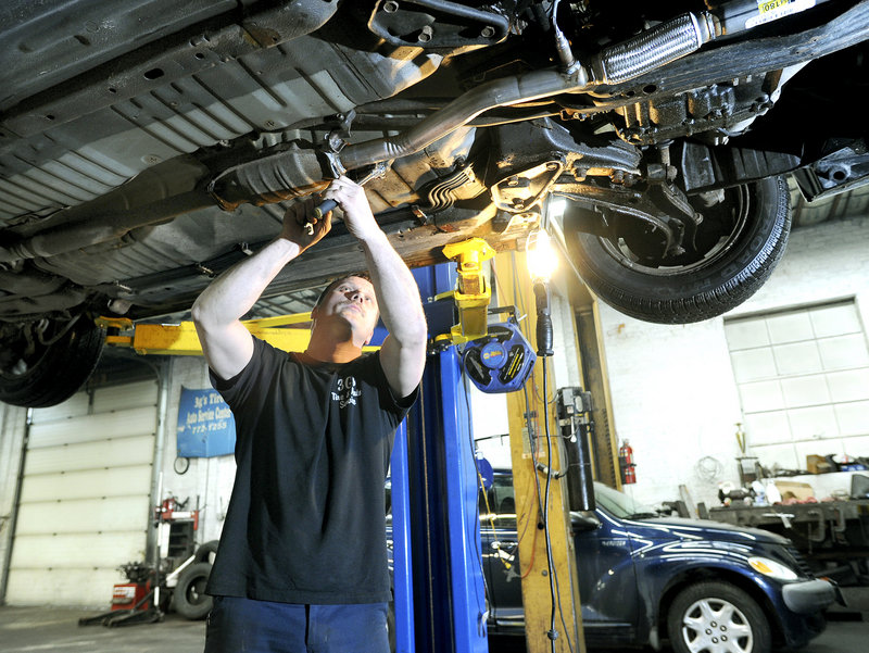 Auto technician Bob Burns installs a new exhaust system on a car at 3G's Tire & Auto Service in Portland. Burns said manufacturers are getting better at sharing information, but it's still difficult for mechanics to acquire scan codes for many ignition and security systems.