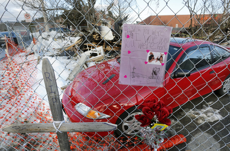 A memorial to Dale Fussell covers a fence at 29 Bluff Road in Bath. Officials believe a loose pipe coupling at the building allowed propane gas to escape, leading to an explosion.