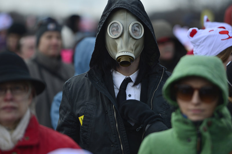 """A man wearing a gas mask joins the crowd gathered Sunday on the National Mall in Washington for the """"Forward on Climate"""" rally."""