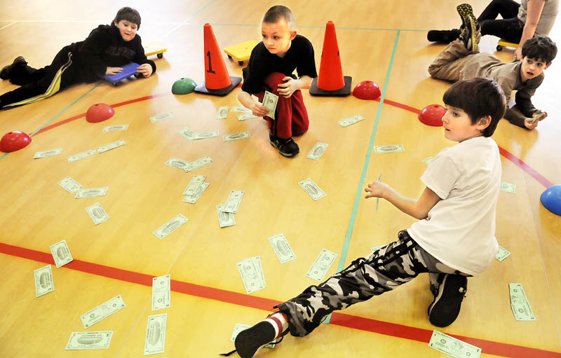 Whitefield Elementary School students roll across the floor of the gym on carts Tuesday, after collecting paper money to practice counting during physical education class.