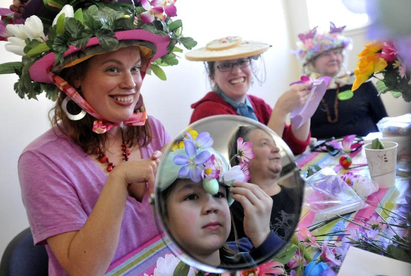 Bria Sanborn, left, Liz Bailey, back center and Beatrice Borden, far right, laugh as Brian Evans, 8, of South Solon, makes the final adjustments to his Easter bonnett in the mirror at the Waterville Easter Bonnett Contest at the Waterville Public Library on Saturday.