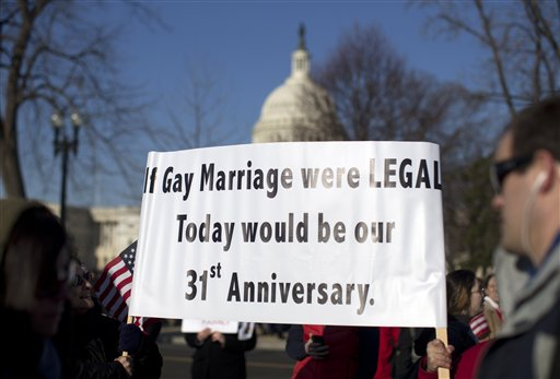 With the Capitol in the background, supporters of gay marriage carry signs in front of the Supreme Court on Wednesday, before the court began hearing arguments on a constitutional challenge to the law that prevents legally married gay Americans from collecting federal benefits generally available to straight married couples.