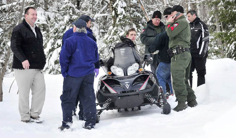 Seventeen-year-old Nicholas Joy is surrounded by game wardens and others that brought him out of the woods Tuesday. Joy spent two night lost in the woods near Sugarloaf ski area. At right is Joseph Paul, who picked up Joy on the snowmobile and at left is Carrabassett Valley police chief Mark Lopez.