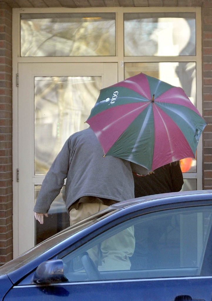 An unidentified man shields Amanda Huard with a striped umbrella as she enters Skowhegan District Court Friday on a sunny morning. Huard is the mother of Kelli Murphy, the 11-year-old charged with manslaughter in the death of an infant last year.