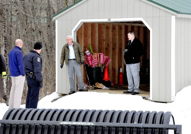 Waterville Police Detective Alan Perkins, center, speaks with Waterville Parks and Recreation Director Matt Skehan, at left, near a shed from which two snowmobiles were stolen, at the Quarry Road Recreation Area, on Monday.
