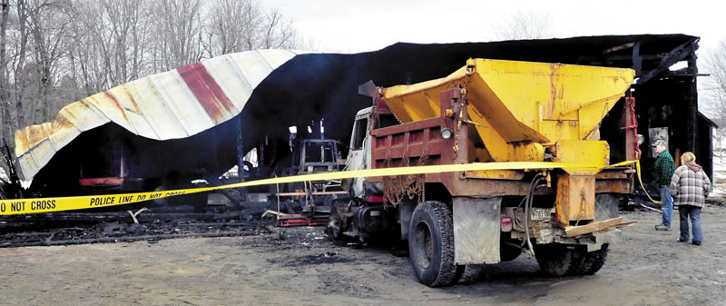 Arthur Kennedy and his friend, Ceri Zeolla, on Sunday look over the burned remains of the Bingham town garage and equipment that was destroyed by fire late Saturday evening. Kennedy said he plows for the town and two of his own plow trucks and a loader were damaged. Kennedy said he believes the fire was intentionally set.