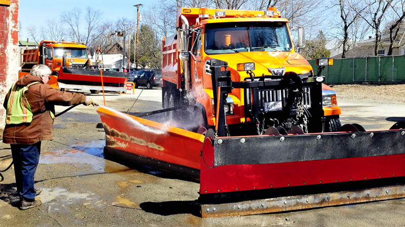 Though it was only a couple days before the official start of spring, Waterville Public Works employee Dan Wilson washes off dirt from one of the city snowplow trucks on Monday. Plows likely will be out in force Tuesday as a significant snowstorm is forecast to dump up to a foot of snow.