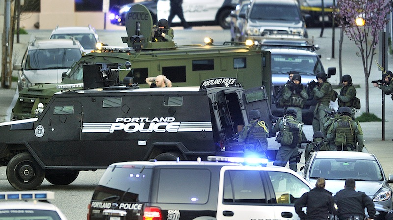 A suspect surrenders – surrounded by Portland police and SWAT Team members – after a standoff on Alder Street in Portland on Monday evening.