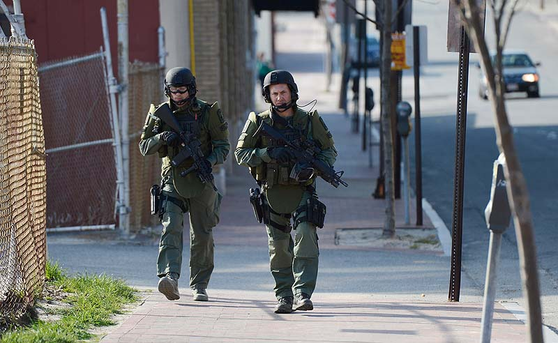 SWAT team members make their way up Preble Street in Portland during a standoff on Alder Street on Monday.