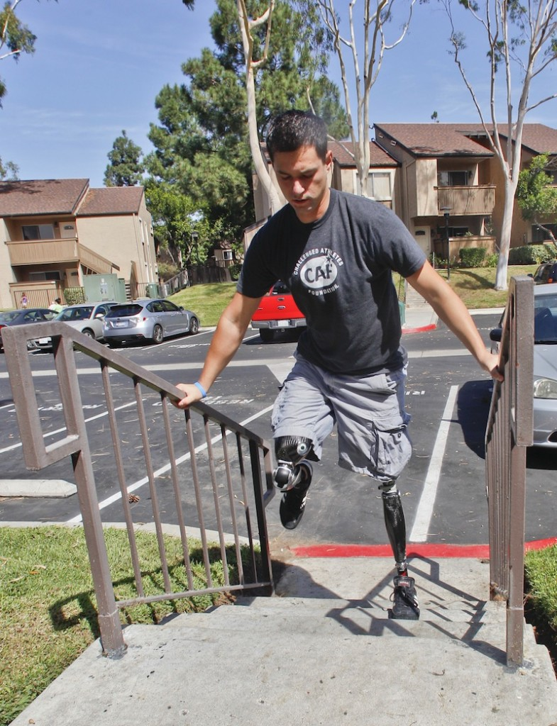 In this Thursday, Oct. 4, 2012 file photo, U.S. Marine Cpl. Daniel Riley, 21, navigates the steps outside his apartment on his prosthetic legs in San Diego, Calif. Riley lost both legs to an IED in Afhganistan. Nearly 2,000 American troops have lost a leg, arm, foot or hand in Iraq or Afghanistan, and their sacrifices have led to advances in the immediate and long-term care of survivors, as well in the quality of prosthetics that are now so good that surgeons often chose them over trying to save a badly mangled leg. (AP Photo/Lenny Ignelzi)