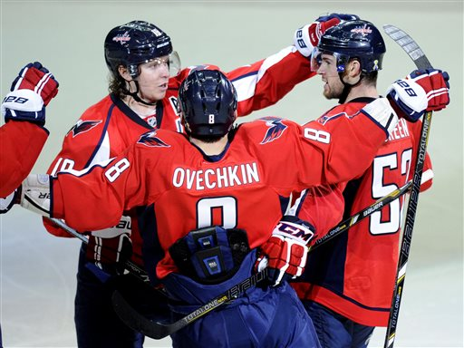 Washington Capitals defenseman Mike Green, right, celebrates his goal with teammates Nicklas Backstrom, left, of Sweden, and Alex Ovechkin (8), of Russia, during the third period of an NHL hockey game against the Boston Bruins, Saturday, April 27, 2013, in Washington. The Capitals won 3-2 in overtime. (AP Photo/Nick Wass)