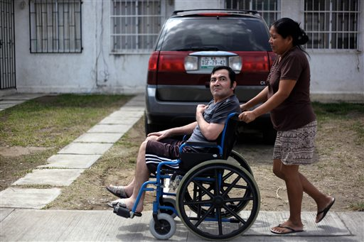 Jacinto Rodriguez Cruz, 49, leaves his home in a wheelchair with the help of his wife, Belen Hernandez, in Veracruz, Mexico, recently. Cruz and another friend suffered serious injuries during a car accident in May 2008 in northwestern Iowa. After their employers' insurance coverage ran out, Cruz, who was not a legal citizen, was placed on a private airplane and flown to Mexico still comatose and unable to discuss his care or voice his protest.