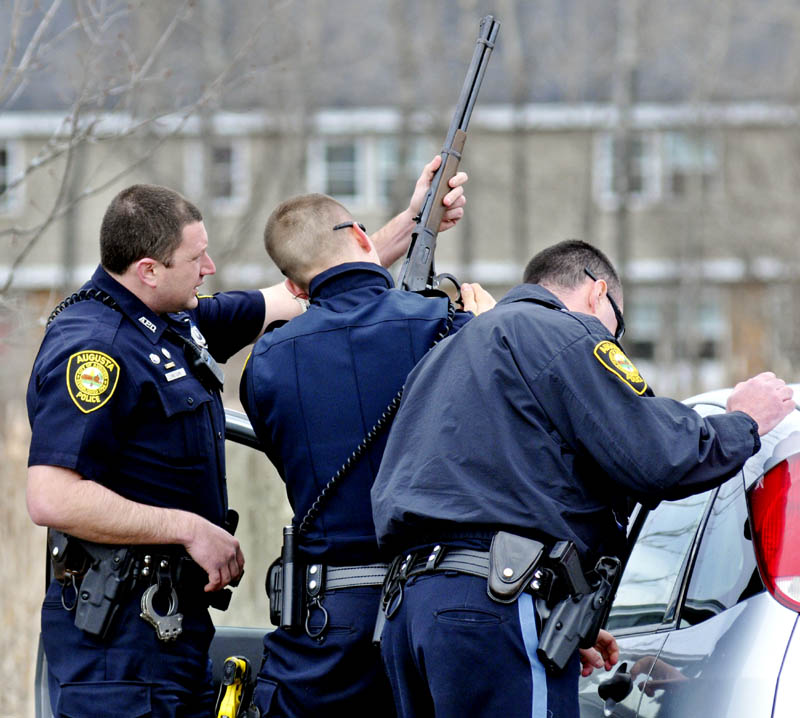 Augusta police officers Nikolas Hample, center, and Eric Lloyd, left, unload a rifle, as Paul Doody searches the vehicle a man was sitting in, Sunday on the Piggery Road. Hample convinced the man, who was alone, to exit the vehicle.