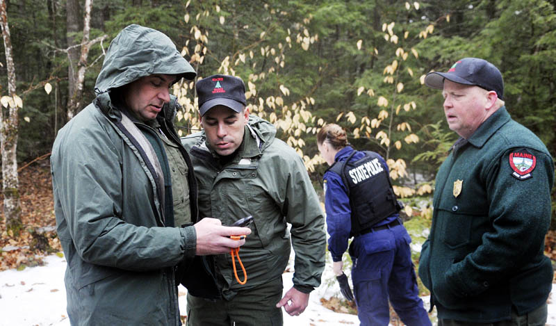 Game wardens and state police retrieve global positioning coordinates before hiking to Christopher Knight's camp in Rome Tuesday.