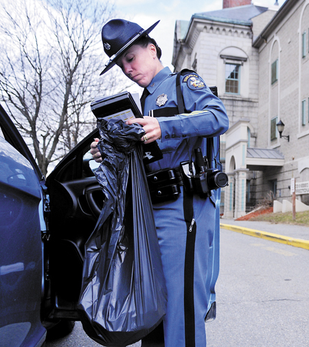 Maine State Police Trooper Diane Perkins-Vance carries a bag of Christopher Knight's clothing she seized from him Sunday, at the Kennebec County jail. Perkins-Vance arrested Knight, alleged to have committed more than 1,000 burglaries while living in the woods for 27 years, on new charges. Knight's bail was increased to $250,000, from $5,000.