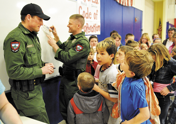 Game Wardens Kris MacCabe, left, and Lt. Shon Theriault sign autographs for students and faculty Monday during a visit to the Belgrade Central School.