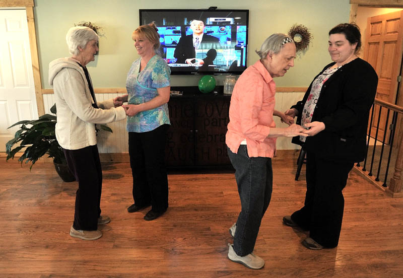 Martha Fabian, far left, dances with Debi Braun, alongside June Meres and Maribeth Beland, far right, in the dayroom at Bedside Manor on Belgrade Road in Oakland on Wednesday. Fabian and Meres are both residents at the 10-bed Alzheimer's care facility in Oakland, operated by Fabian's son, E.J Fabian, and daughter, Julie Benecke.