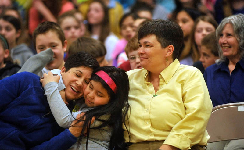 Marisa Weinstein, left, music teacher at Warsaw Middle School, gets a hug from her daughter, Marta, 8, center, and partner, Marilyn Buzy, right, after she was presented the Maine Music Educators Association Educator of the Year award during a surprise assembly at the Pittsfield school on Tuesday.