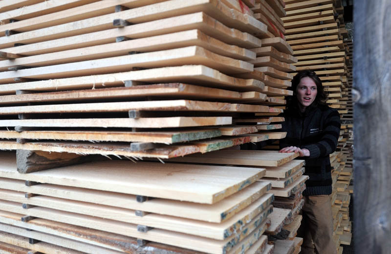 Bjarki Gunnarson, 25, inspects a stack of finished lumber at The Wood Mill of Maine on Mercer Road in Mercer on Friday.