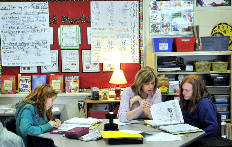 Karen Mayo, a fifth-grade teacher at the James H. Bean School in Sidney helps two students Jade Veillaux, 11, right, and Macey Eubank, 10, left, on Wednesday. James H. Bean is one school in the area that has implemented a mass customized learning program that integrates up to three grade levels in one classroom.