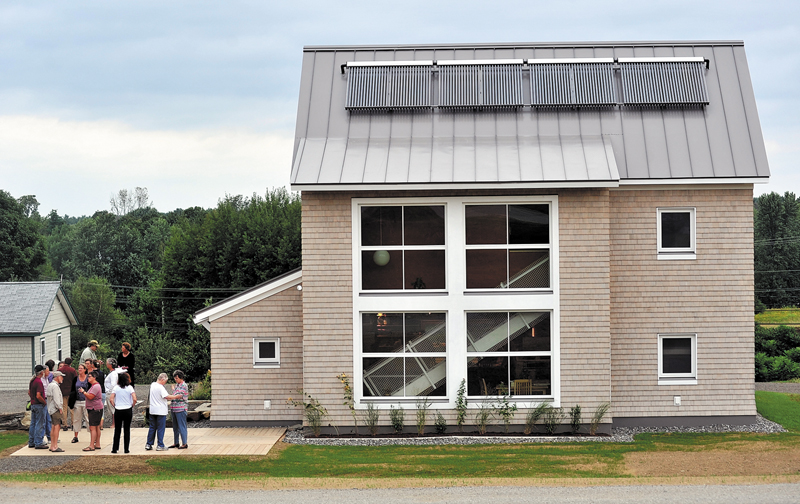 Members of Untiy College faculty and staff along with members of media stand outside the Terra House at Untiy College.