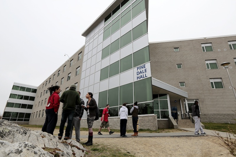 UMASS-Dartmouth students stand outside he Pine Dale Hall dormitory that Dzhokhar Tsamaev, lived in on Friday, April 19, 2013 in Dartmouth, Mass., as students were evacuated from campus on Friday, April 19, 2013, as local and state officials investigate the dorm room of Tsarnaev, 19, one of the two suspects wanted for the Boston Marathon bombing on Monday. The campus closed down along with colleges around the Boston area. (AP Photo/Standard Times, Peter Pereira) crime;terrorism;bomb;investigation;police;military