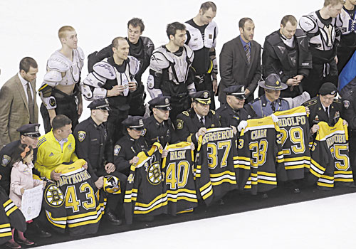 THANK YOU: First responders, members of law enforcement and Boston Marathon officials hold Boston Bruins jerseys as they gather with members of the team, back, on the ice following the Bruins game against the Florida Panthers on Sunday at the TD Garden in Boston. In a change requested by fans, Bruins players presented their jerseys to some of those who offered help in the minutes and days following the marathon bombings on Monday.