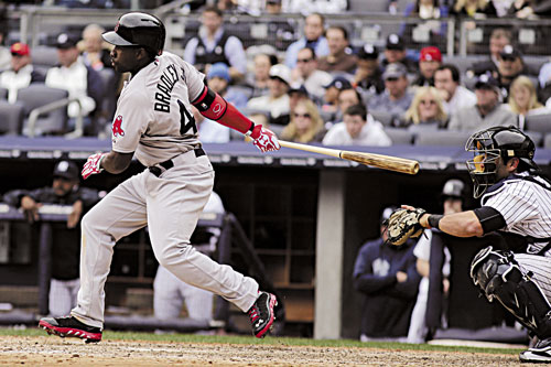 GOOD DEBUT: Boston's Jackie Bradley Jr., left, follows through after hitting an RBI groundout as New York Yankees catcher Francisco Cervelli looks on during the seventh inning Monday in New York. Bradley went 0-for-2 with three walks, two runs and one RBI.