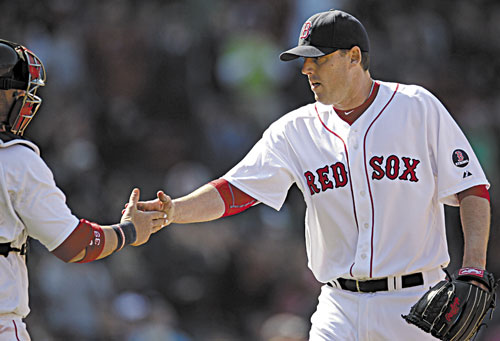 GOOD OUTING: Boston Red Sox starting pitcher John Lackey, right, is congratulated by catcher Jarrod Saltalamacchia after the last out in the sixth inning against the Houston Astros on Sunday at Fenway Park in Boston. Lackey earned his first win in the majors since 2011, allowing one run on five hits while striking out four and walking two.