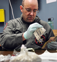 Kennebec County Sheriff's Det. Sgt. Frank Hatch counts money seized during a raid in Farmingdale conducted on Tuesday that resulted in the recovery of more than 100 grams of heroin, in plastic bags. Deputies, agents from the Maine Drug Enforcement and the federal Drug Enforcement Agency arrested four people while seizing the drugs and money from an apartment on Hill Street. The heroin could be packaged sold as approximately 5,000 doses, according to Hatch, with a street value in excess of $50,000.