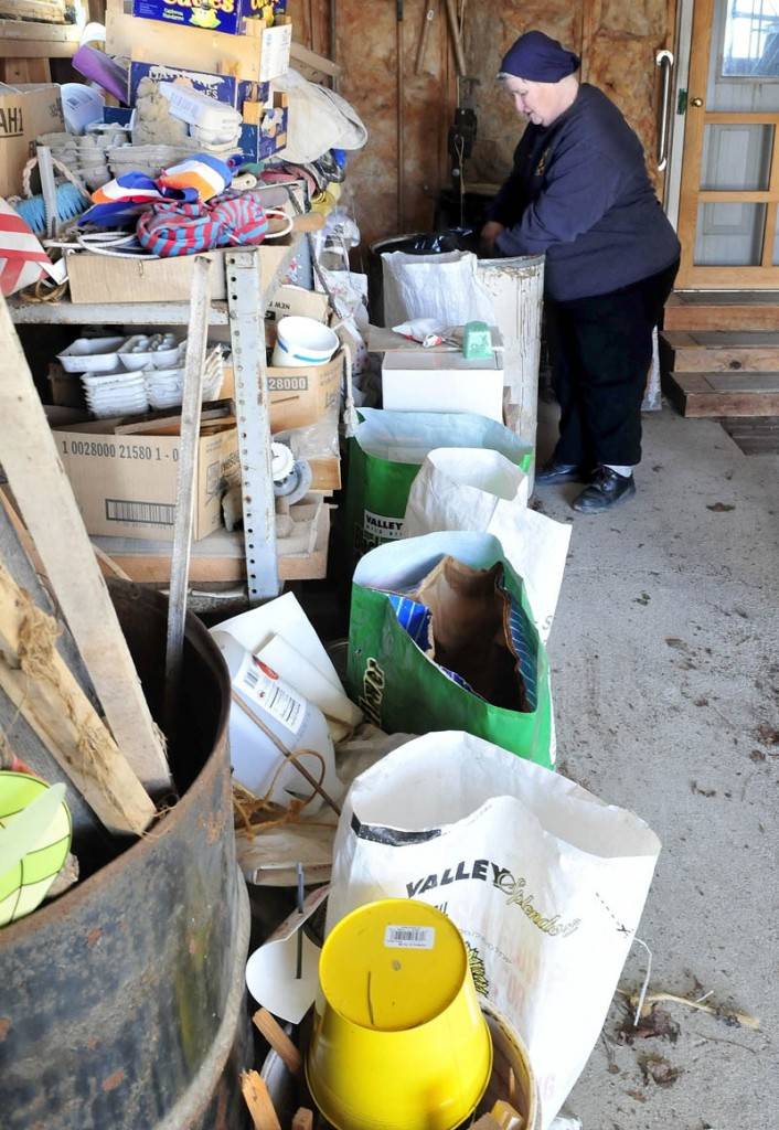 Joan Sheldon, of Knox, a board member of the Unity Area Regional Recycling Center, sorts through a bag of material that cannot be recycled, next to several containers of recyclable materials. Sheldon said her efforts to reuse materials leaves her with only three bags of trash a year.