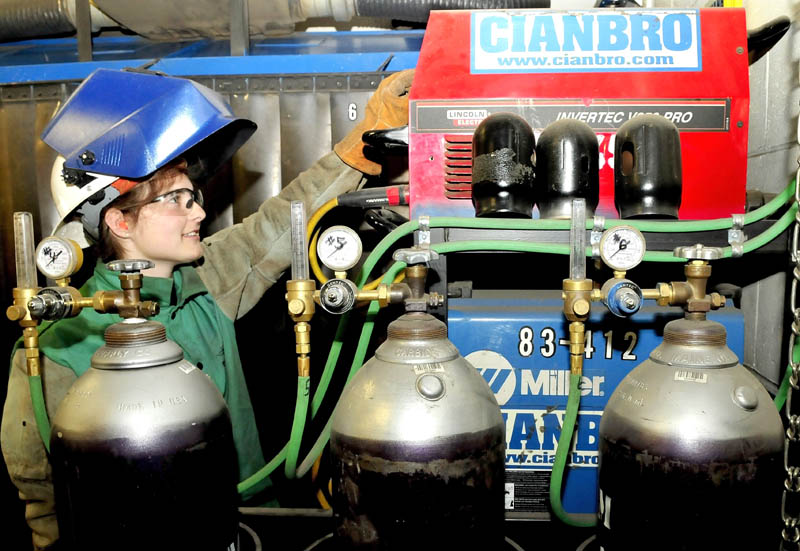 Skowhegan Area High School student Sarah Finnemore increases amperage on equipment before doing some welding in the training center at the Cianbro company in Pittsfield on Tuesday.