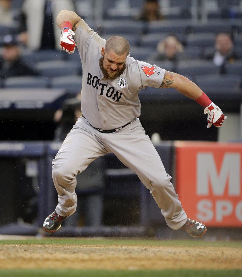 Boston's Jonny Gomes is clearly pumped after scoring on a two-run, ninth-inning single by Jacoby Ellsbury during the Red Sox season-opening 8-2 win over New York at Yankee Stadium on Monday.