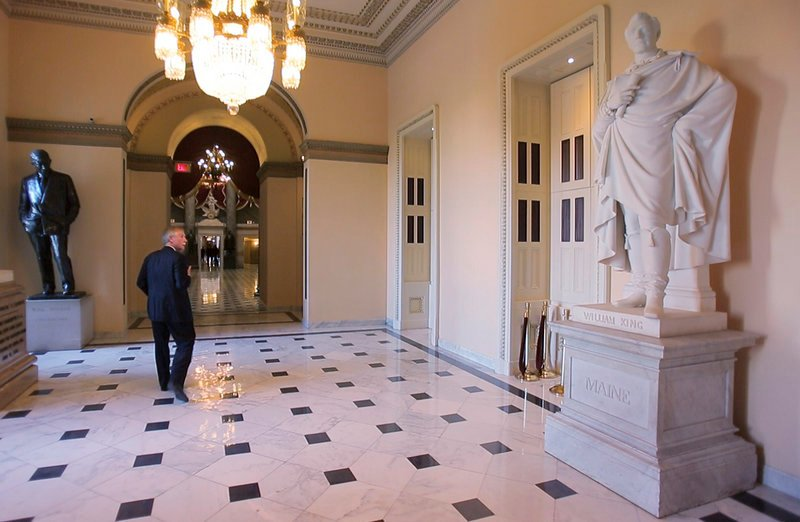 """The senator strolls past a larger-than-life statue of William King – Maine's first governor – in the Capitol's Statuary Hall on Thursday. For an unabashed student of history, there simply is no better place on Earth to report for work each day. Says the 69-year-old senator: """"The circumstances call forth the energy."""""""