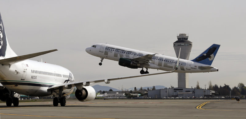 One jet departs in view of the air traffic control tower at Seattle-Tacoma International Airport as another waits on the tarmac Tuesday. The bill permits the Transportation Department to transfer $253 million from other parts of the agency.