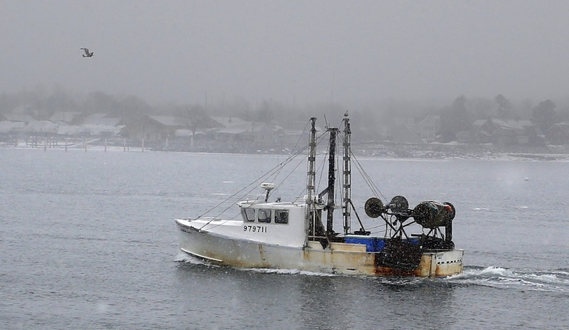 In this Jan. 28, 2013, photo, a groundfishing boat makes its way back toward shore near the Portland Fish Pier. A bill in the Legislature would let the state's dwindling groundfishing fleet keep lobsters that come up in trawl nets and sell them in states that allow such lobsters to be landed.