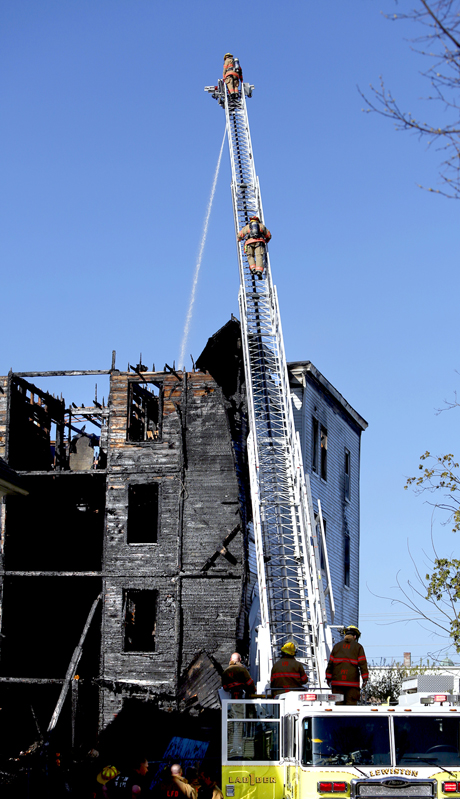 Firefighters spray water on the roof of a vacant apartment building on Bartlett Street in Lewiston on May 6, 2013 following a third major fire in eight days in the downtown area.