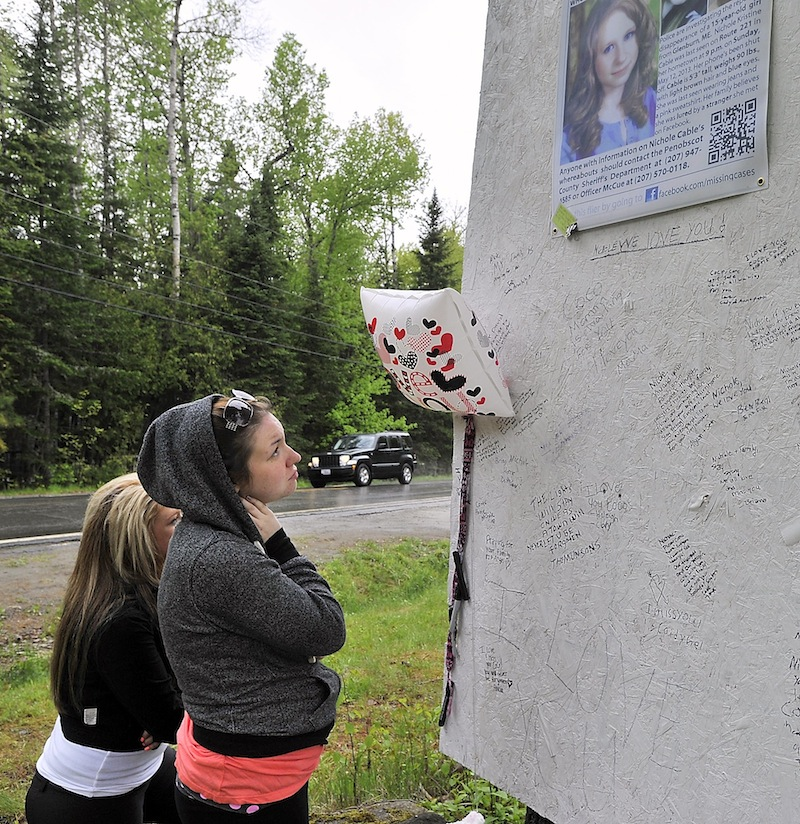 Cousins Ashley Look, left, and Alicia Eaton view the notes left by friends and relatives as they visit the memorial to Nichole Cable who was allegedly murdered by an acquaintance. Photographed on Tuesday, May 21, 2013,
