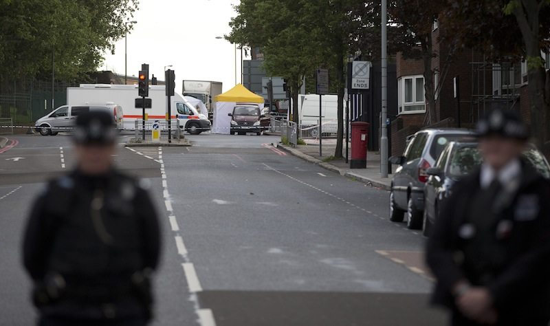 Police cordon off the scene of an attack which has left one man confirmed dead and two people wounded near Woolwich barracks in London Wednesday, May, 22, 2013. Scotland Yard said officers responded to reports of an assault Wednesday afternoon in the London neighbourhood of Woolwich. London Ambulance service said one man was found dead at the scene and two other men were taken to the hospital, with one in serious condition.(AP Photo/Alastair Grant)