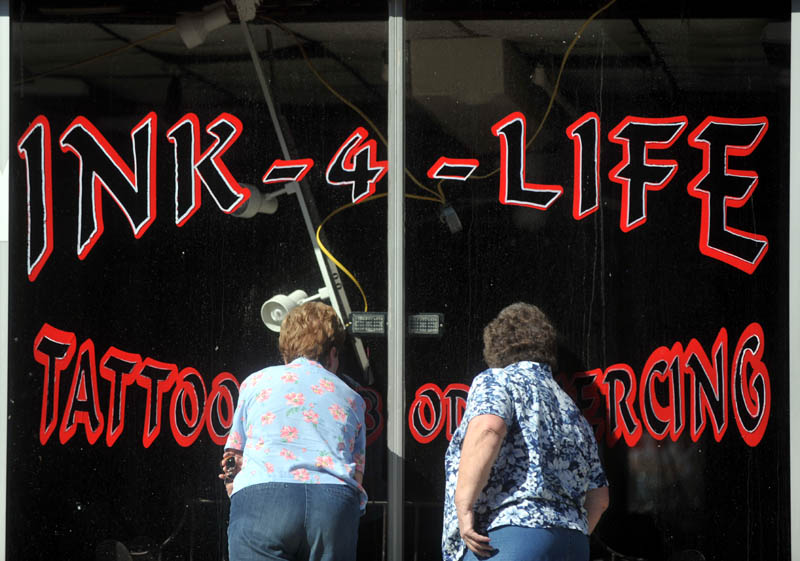 People peer into Ink-4-Life, on the first floor of a building on Main Street, Saturday morning.