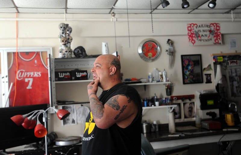 Bill Juliano reacts as he looks around his fire-damaged tattoo studio, Ink-4-Life, Saturday morning.