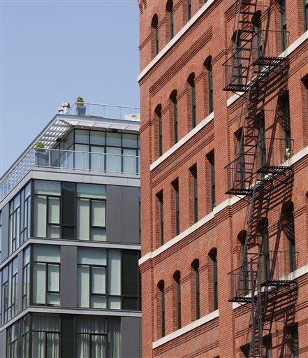 A modern luxury glass apartment building, left, sits across the street from an older red brick apartment, the home of photographer Arne Svenson.