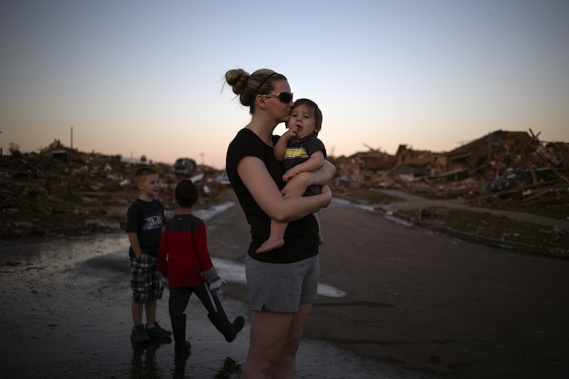 Rae Kittrell holds her son Rylan, who turned one-year-old today, a block away from her house in Moore, Oklahoma, two days after the Oklahoma City suburb was left devastated by a tornado on May 22, 2013. Kittrell's house survived the tornado. Tornado survivors thanked God, sturdy closets and luck in explaining how they lived through the colossal twister that devastated an Oklahoma town and killed 24 people, an astonishingly low toll given the extent of destruction. (REUTERS/Adrees Latif) :rel:d:bm:GF2E95N04TH01