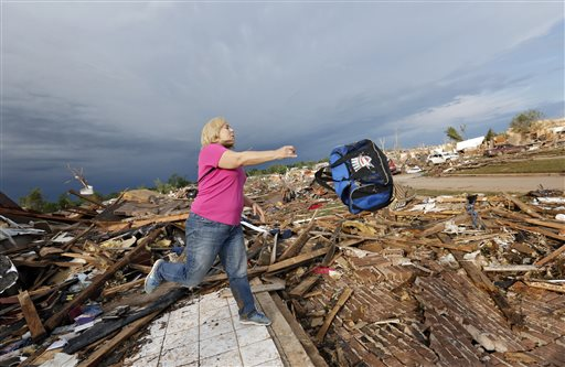 Penny Phillips throws out a bag of salvaged clothing as she goes through the remains of her home on Tuesday in Moore, Okla.